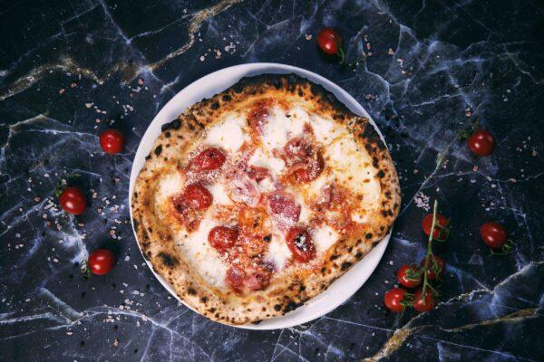 na białym talerzu pizza z bufalą pomidorkami i włoskim boczkiem, na cienkim cieście z grubymi brzegami pizza Napolitańska jedyna w Krakowie