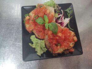 Na stalowym stole czarny talerz z dwiema kromkami domowego chleba, posypany świeżym pomidorem, oliwą z oliwek z pierwszego tłoczenia i świeżą bazylią.