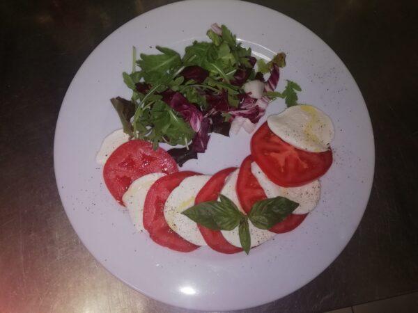 Na bialym talerzu kompozycja krazkow mozzarelli di bufala z soczystymi czerwonymi pomidorami doprawiona oliwa z oliwek i udekorowana listkami bazylii