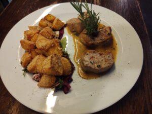 Na białym talerzu polędwiczki wieprzowe w sosie z zielonego pieprzu z opiekanymi w rozmarynie ziemniakami z zielona sałatą do zobaczenia w Krakowie