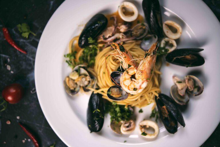 duży talerz w białym kolorze ze spaghetti z owocami morza, krewetki, calmary, mule, oprószone pietruszka zieloną. do Krakowa zapraszamy na to danie do krakowa
