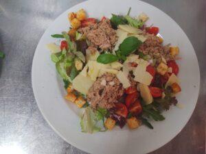 Na dużym białym talerzu, zielona sałata z tuńczykiem pomidorkami koktajlowymi, grzankami rozmarynowymi z oliwą z oliwek tak zjesz tylko w Krakowie