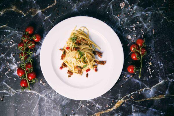 Na białym dużym płaskim talerzu makaron Linguine z pomidorkami. Jak makaron to w krakowie