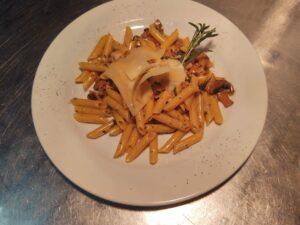 Na białym talerzu makaron penne (rurki ukośnie cięte boki) z włoską kiełbasą salcicia, pieczarkami , rozmarynem i odrobiną słodkiej śmietanki zjesz też w Krakowie