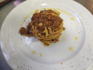 su un piatto di portata bianco tagliatelle al ragu Bolognese