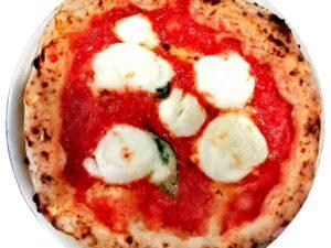 Na cienkim cieście z grubymi brzegami napolitańska pizza Margherita (sos pomidorowy, płatki mozzarella oraz żwieża bazylia na koniec kilka kropli oliwy z oliwek i gotowe takie danie włoskie w Krakowie