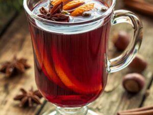 w przeżroczystej szklance z uszkiem grzane wino z goździkami, cynamonem i pomarańczami na zimowe wieczory w krakowie