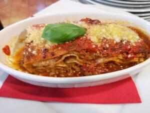 Na białym owalnym talerzu bolońska lasagne z parmezanem na wierzchu, sosem bolońskim i listkiem bazylii.