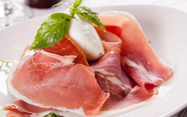 Na białym talerzu pachnąca szynki parmenka z kuleczką mozzarella z listkami bazylii