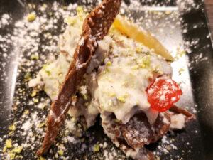 na czarnym talerzu sycylijskie cannoli rozłożone ricottą z mleka owczego, kandyzowaną skórką pomarańczy i wiśni, łamanymi goframi i kaszą pistacjową