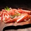 Italian prosciutto crudo or jamon with rosemary. Raw ham on wood
