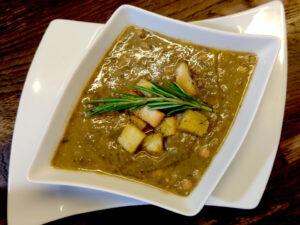 na drewnianym stole biały talerz zawierający zupę z ciecierzycy, soczewicy i ziemniaków